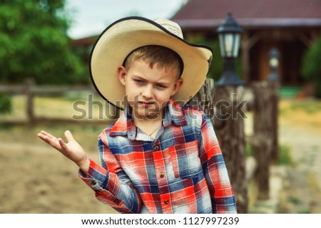 portrait of a boy in a straw hat and plaid shirt on a ranch
