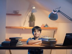 Portrait of a boy in his room at a work table. Emotion of satisfaction and zeal on the child's face