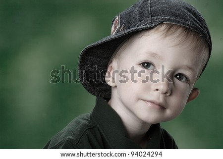 portrait of a boy in the cap is green background
