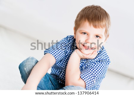 portrait of a boy in the living room, sitting on the floor - stock photo