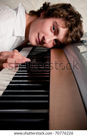 Portrait of a boy lying on a piano keyboard