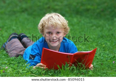 Portrait of a boy lying on the grass with a book in the park.
