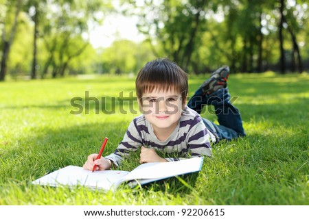 Portrait of a boy lying on the grass with a book in the park - stock photo