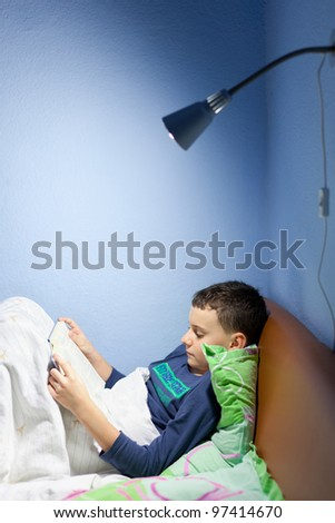 Portrait of a boy reading a book at bedtime, lying in his bed