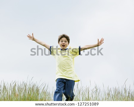 Portrait of a boy running with his arms outstretched