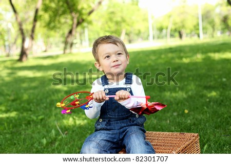 Portrait of a boy sitting on the basket in the park