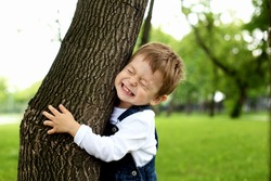 Portrait of a boy standing near the tree in the park