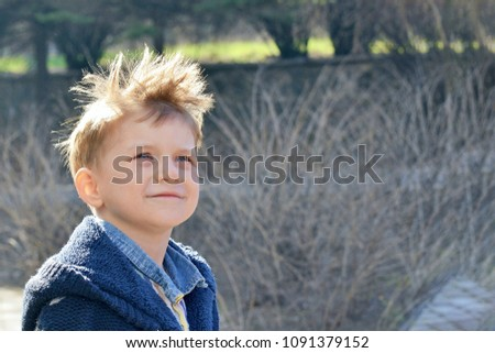 Portrait of a boy with an interesting facial expression outdoors outdoors, outdoors, child in the park.