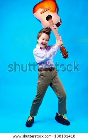portrait of a boy with guitar on the blue background