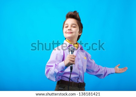 portrait of a boy with microphone on the blue background