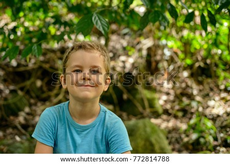 Portrait of a boy 6 years old cheekily smiles against a background of green  foliage outdoor