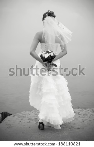 Portrait of a bride with a wedding bouquet on the coast of the sea. Outdoor black and white shot