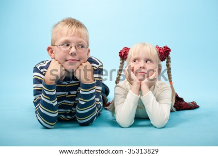 Portrait of a brother and sister lying down on floor