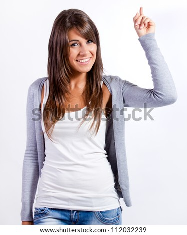 Portrait of a brunette pointing up against white background