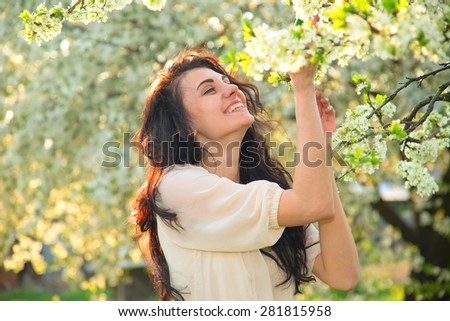 Portrait of a brunette woman inhales the scent of flowers. Happy woman enjoying the scent of blooming flowers on the tree. Young beautiful happy girl. She rests and enjoys the scent of flowers. Story.