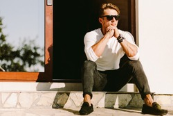 portrait of a brutal handsome man in sunglasses and watch outdoors at home. Stylish man wearing casual. Men's beauty, fashion. Optics for men.
