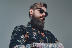 Portrait of a brutal man with sunglasses wearing stylish clothing with watch in gray background. Handsome guy in retro style.
