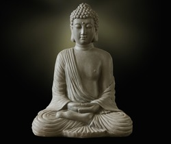 Portrait of a buddha statue, islated on dark background. Sign for peace and wisdom