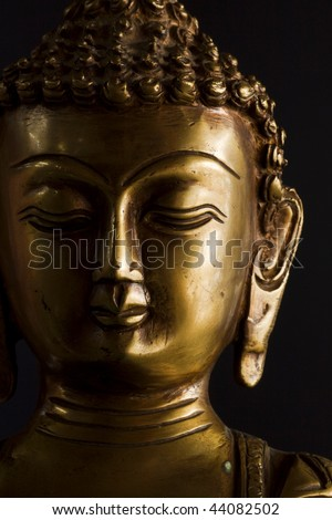Portrait of a buddha statue with black background.
