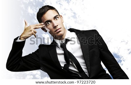 portrait of a business man gesturing suicide against a cloudy sky background
