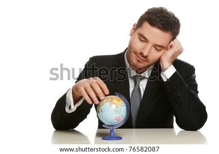 Portrait of a business man sitting by his desk and holding a globe model, isolated on white