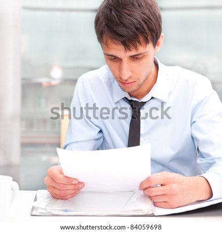 Portrait of a business man working at his office with papers