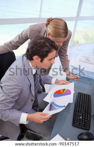 Portrait of a business team looking at a graph in an office