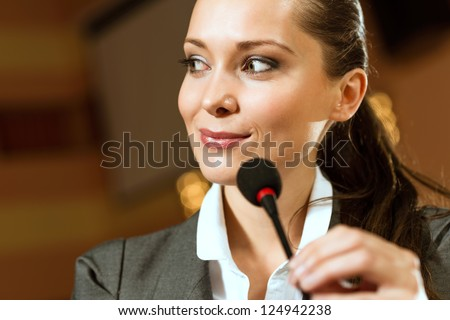 Portrait of a business woman holding a microphone and looks ahead
