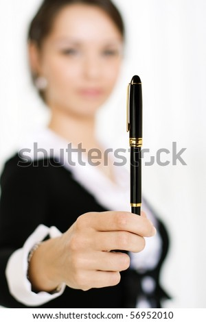 Portrait of a business woman holding pen in her hand, focus on pen