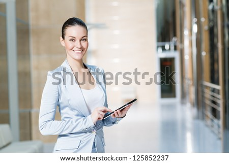 Portrait of a business woman in the tablet at the office, turned around and looking at the camera