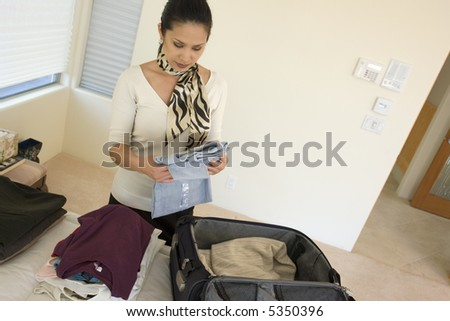 Portrait of a business woman packing her suitcase for a trip