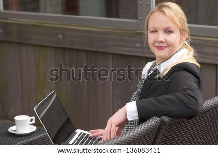 Portrait of a business woman relaxing with laptop and cup of coffee outdoors