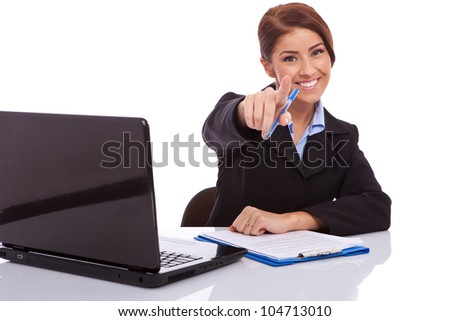 portrait of a business woman sitting at a desk with a laptop, pointing to the camera