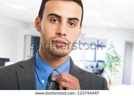 Portrait of a businessman adjusting his necktie