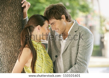 Portrait of a businessman and a businesswoman being affectionate and holding their foreheads together while leaning on a tree outdoors.