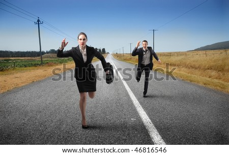 Portrait of a businessman and a businesswoman running on a countryside street