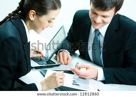Portrait of a businessman and a businesswoman sitting at table and discussing business documents