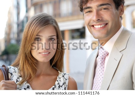 Portrait of a businessman and a businesswoman standing together in a classic office buildings street, smiling.