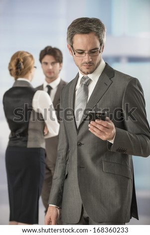 portrait of a businessman at phone in workplace