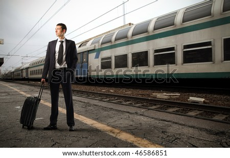 Portrait of a businessman carrying a suitcase standing on the platform of a train station