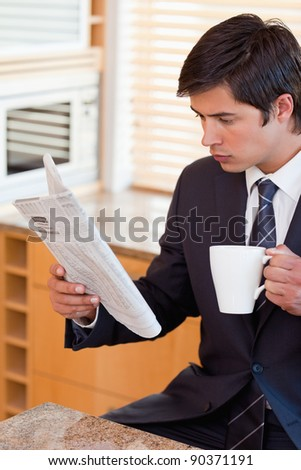 Portrait of a businessman drinking tea while reading the news in his kitchen