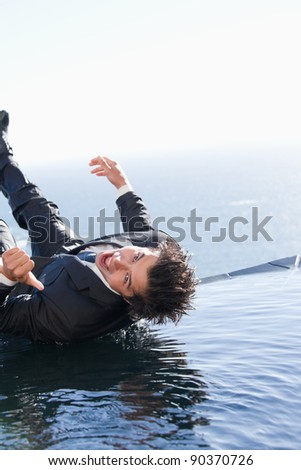 Portrait of a businessman falling into water with the thumb up