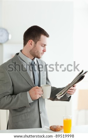 Portrait of a businessman having breakfast while reading the news in his kitchen
