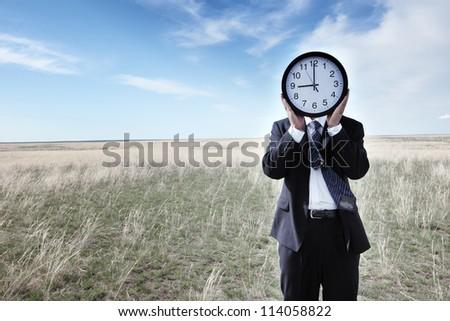 Portrait of a businessman holding a clock on grassland