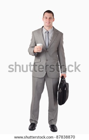 Portrait of a businessman holding a cup of coffee and a computer bag against a white background