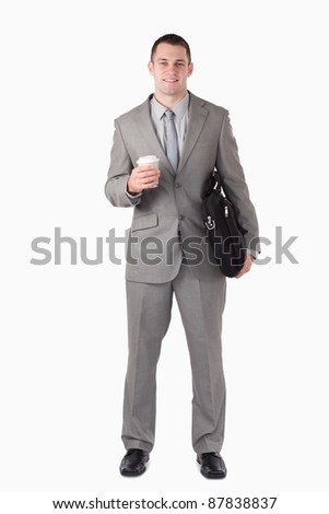 Portrait of a businessman holding a cup of tea and a computer bag against a white background