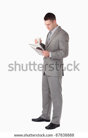 Portrait of a businessman holding a cup of tea while reading the news against a white background