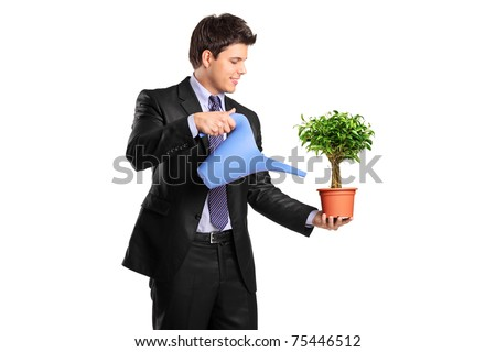 Portrait of a businessman holding a flower pot with benjamin and watering can isolated on white background