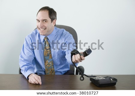 Portrait of a businessman holding a telephone handset and smiling