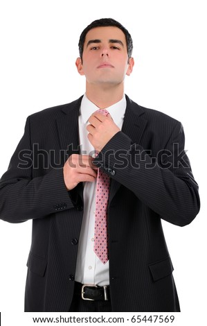 Portrait of a businessman in a dark suit touching up a tie